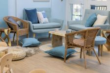 Adult seating in this space looks like a living room. There are two blue sofas and two wicker chairs surrounding a natural wood coffee table. There are rugs on the floor, cushions and a seat pad