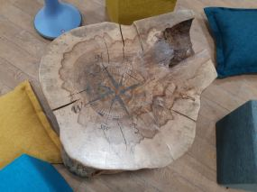 A rustic table with a compass image on the top