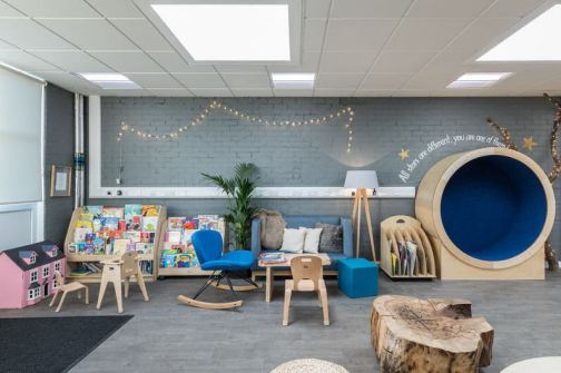 the general purpose room has a library corner which is like a living room, a circular nook is against the wall for a child to sit in, a sofa and rocking chair are beside a coffee table and a lamp and plant create a homely look