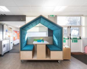 a house shaped meeting space on wheels, there are two benches facing each other over a table and gives a little privacy