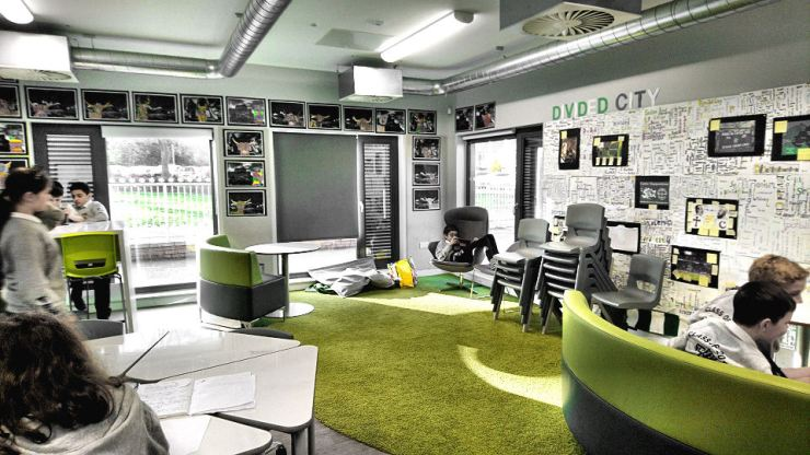 a comfy area of the classroom with a green carpet and round green grey sofas.