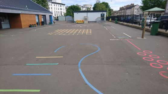 a tarmac playground with colourful line markings that create a fitness circuit
