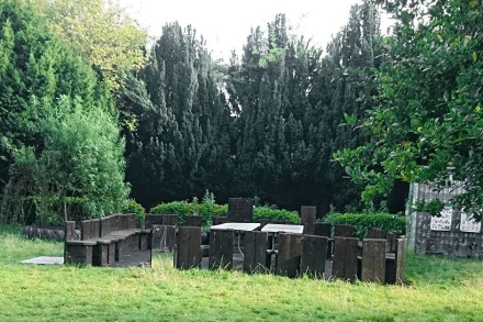 wooden chairs are arranged in a circle outside on the grass