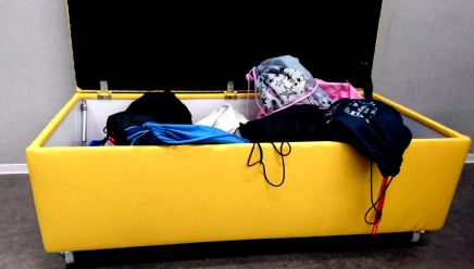 a yellow ottoman on wheels stores the PE bags