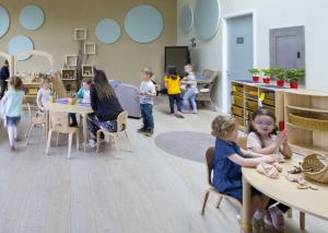 children are sitting at tables working in the nursery