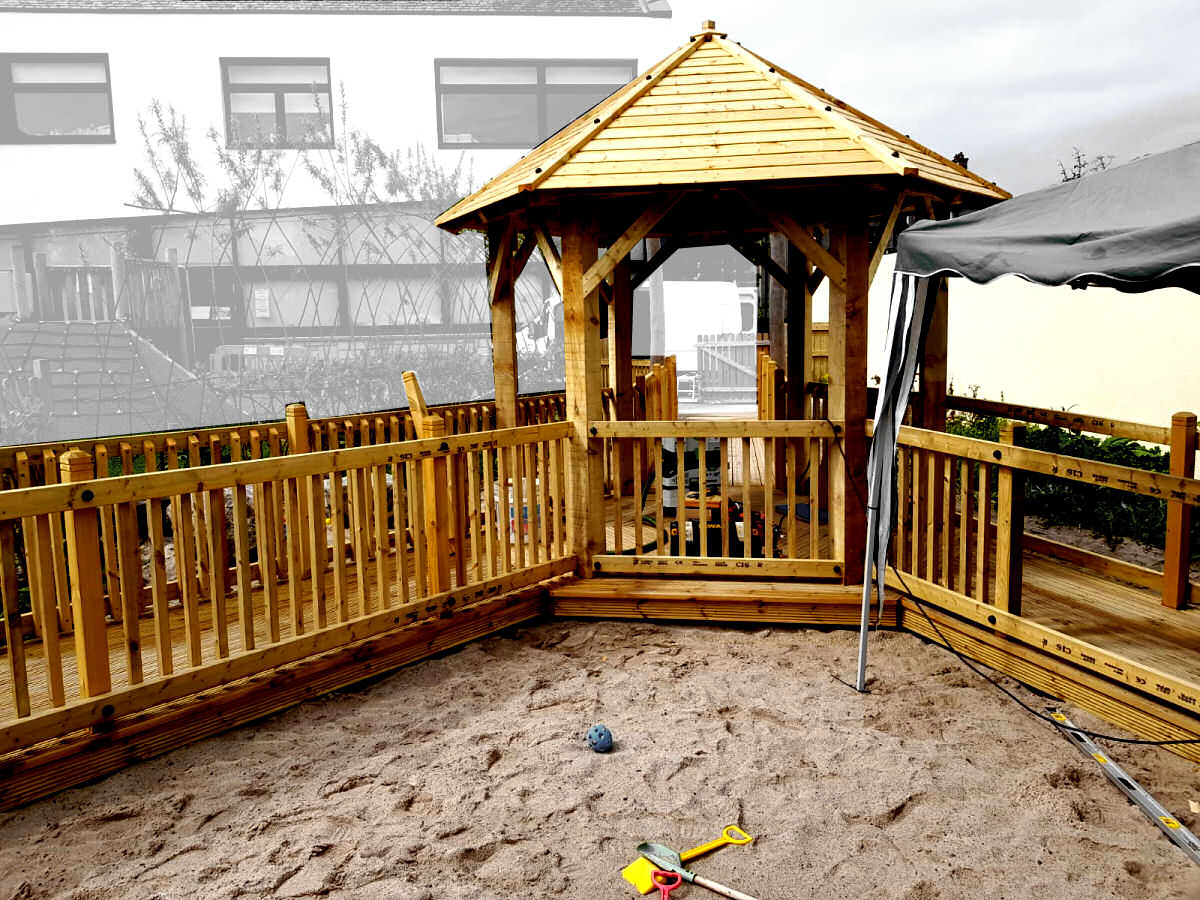 sandpit with a wooden walkway and roofed seating area