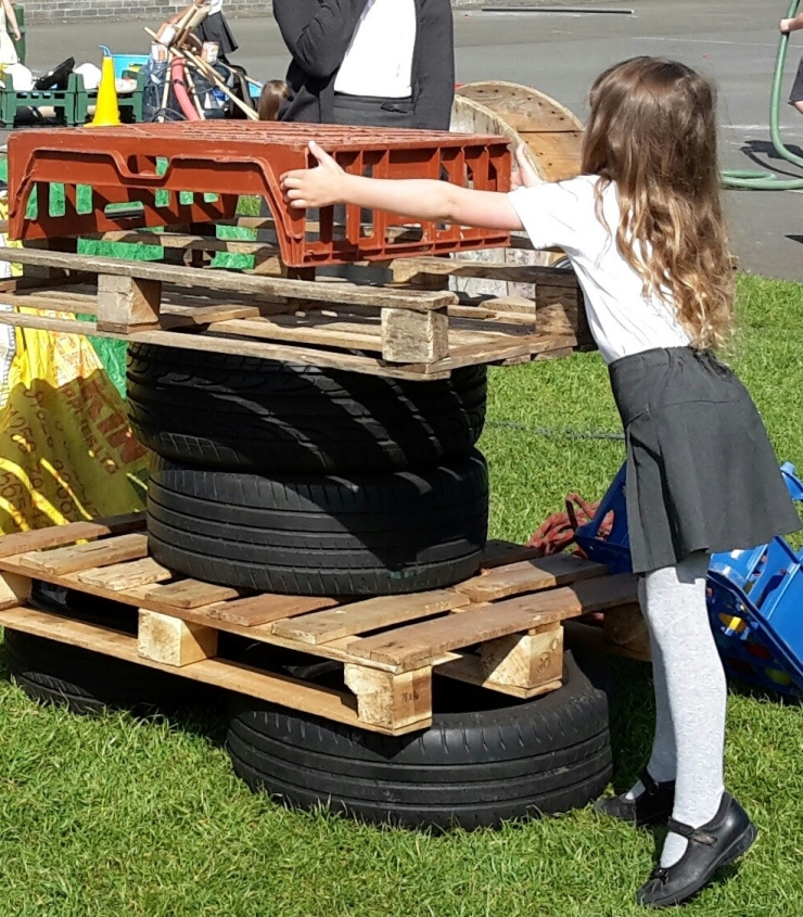 girl build a tower from tyres, palettes and crates