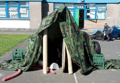 A den made from cardboard, tarpaulin, crates and tyres