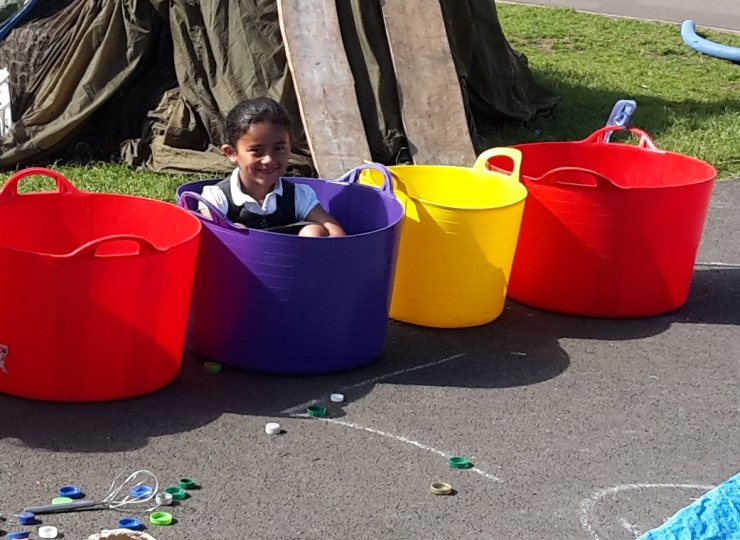 A girl sits in a trug