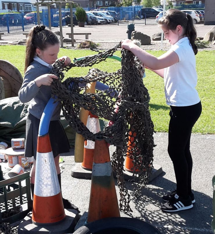 two girls work together to lay netting over a frame made of cones