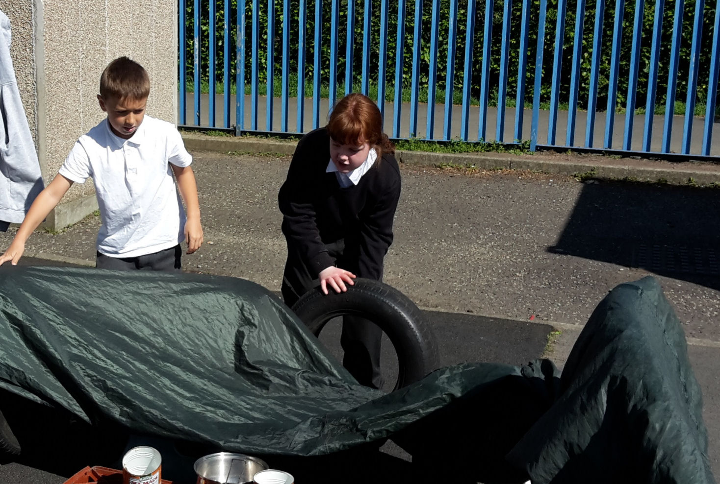 a boy and girl work together to build a den with material and tyres