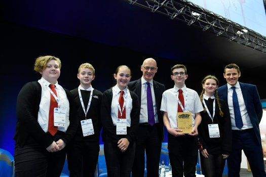 five young people from Broughton High School pose with their trophy alongside Depute First Minister John Swinney, and Richard Park from HUB South East