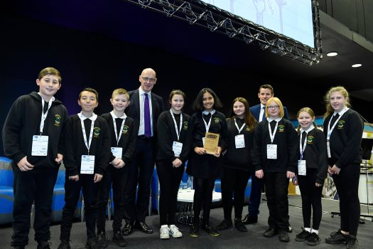 Nine children from Murrayburn primary pose with their trophy alongside Depute First Minister John Swinney, and Richard Park from HUB South East