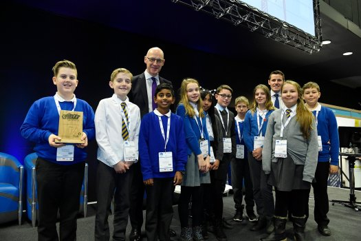Ten children from St Cuthbert's primary pose with their trophy alongside Depute First Minister John Swinney, and Richard Park from HUB South East