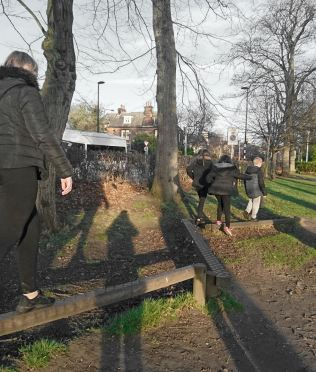 four young people balance on a trim trail