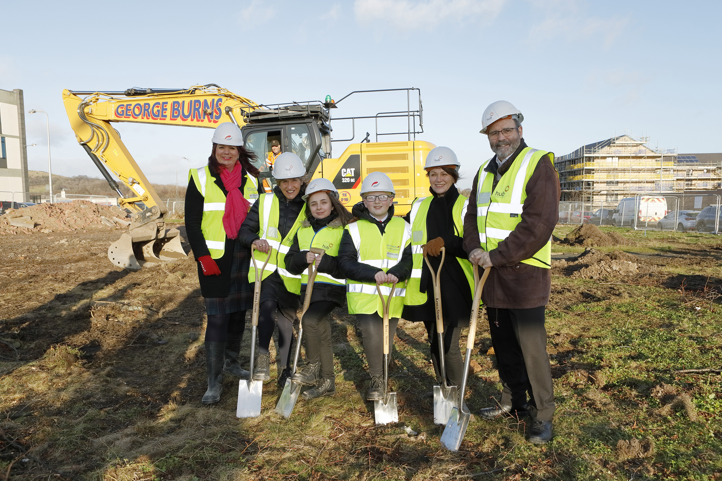 Councillors, staff and students stand on the site of the new school holding spades
