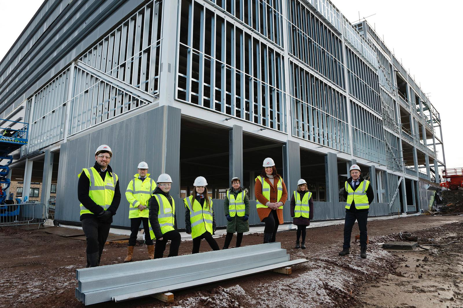 students and project team stand outside the new school in construction