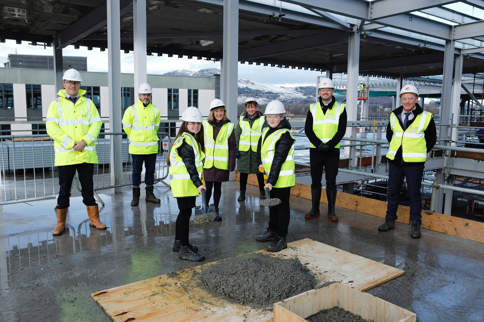 students stand with spades of cement for the Topping out ceremony of the new school